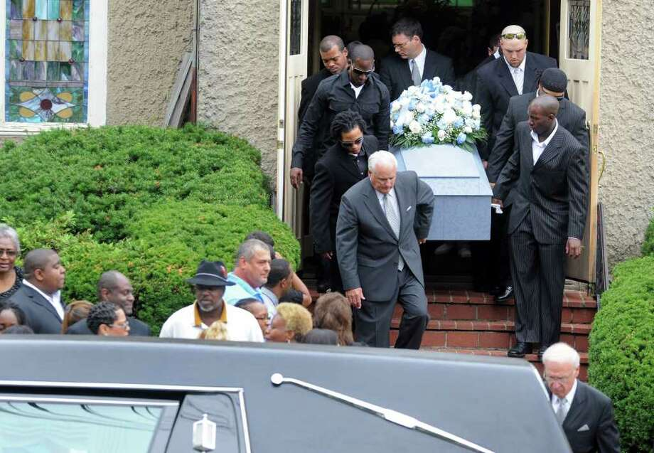 Pallbearers carry Darnell Cooks' casket out of Evangel Temple Church of God in Christ, in Ansonia, following funeral services Friday, June 24, 2011. Cooks, a teammate of Nigel Ingram, was the third member of the 2002 and 2003 Ansonia state champion football teams to die. Photo: Autumn Driscoll, ST / Connecticut Post