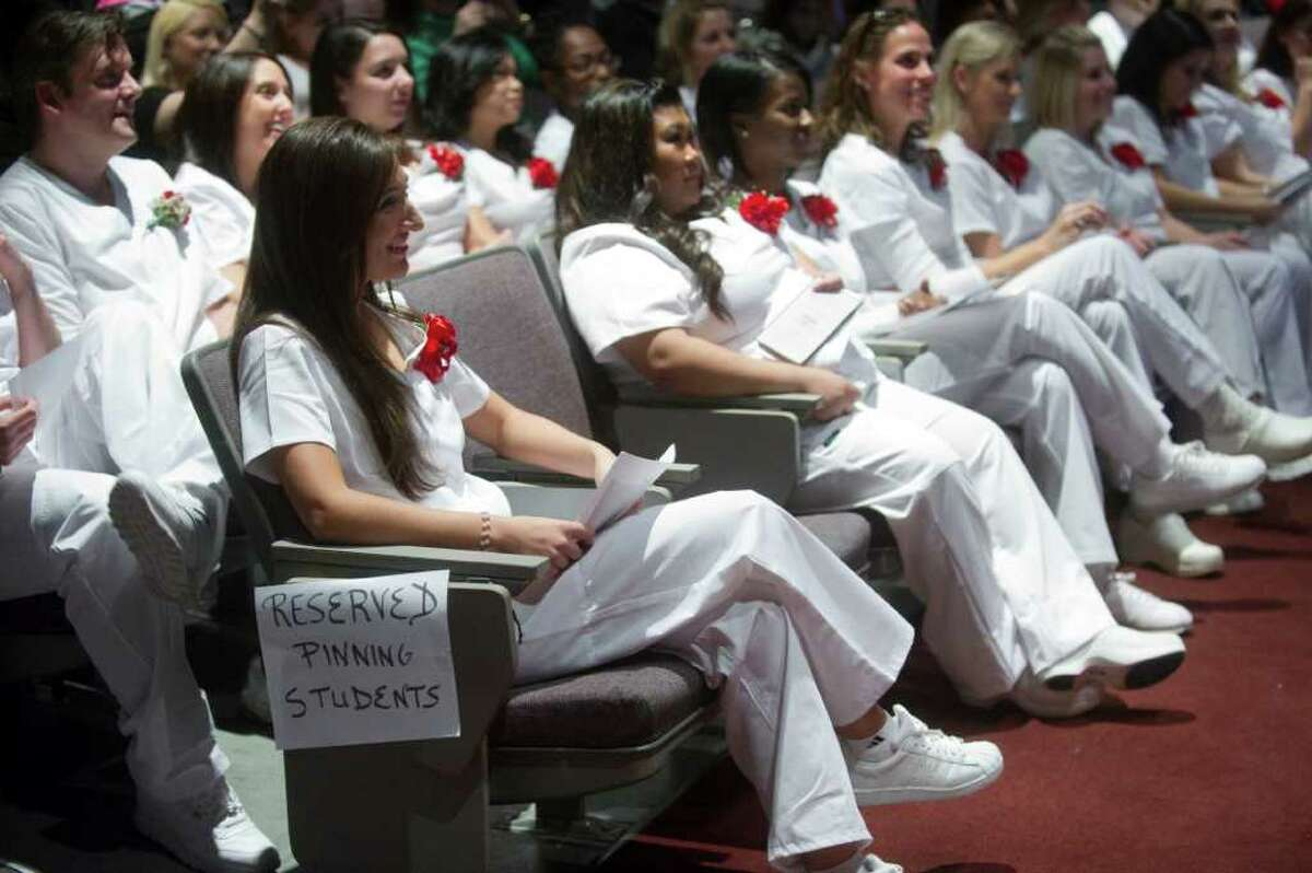 The Norwalk Community College Division of Nursing and Allied Health's annual fall Pinning Ceremony in the school's Pepsico Theater in Norwalk, Conn., December 20, 2011. The ceremony is a tradition in which nursing pins are presented to nursing graduation candidates prior to their graduation from NCC.The pinning ceremony represents the symbolic welcoming of newly graduated nurses into the nursing profession. The new nurses are congratulated by the college's nursing faculty, receive a school pin, and participate in a candle lighting ceremony.The tradition dates back 1,000 years and began as a Maltese cross, a symbol of Christianity. Over the centuries, the cross became a coat of arms and eventually morphed into a design that signifies the school from which the nurse has graduated.