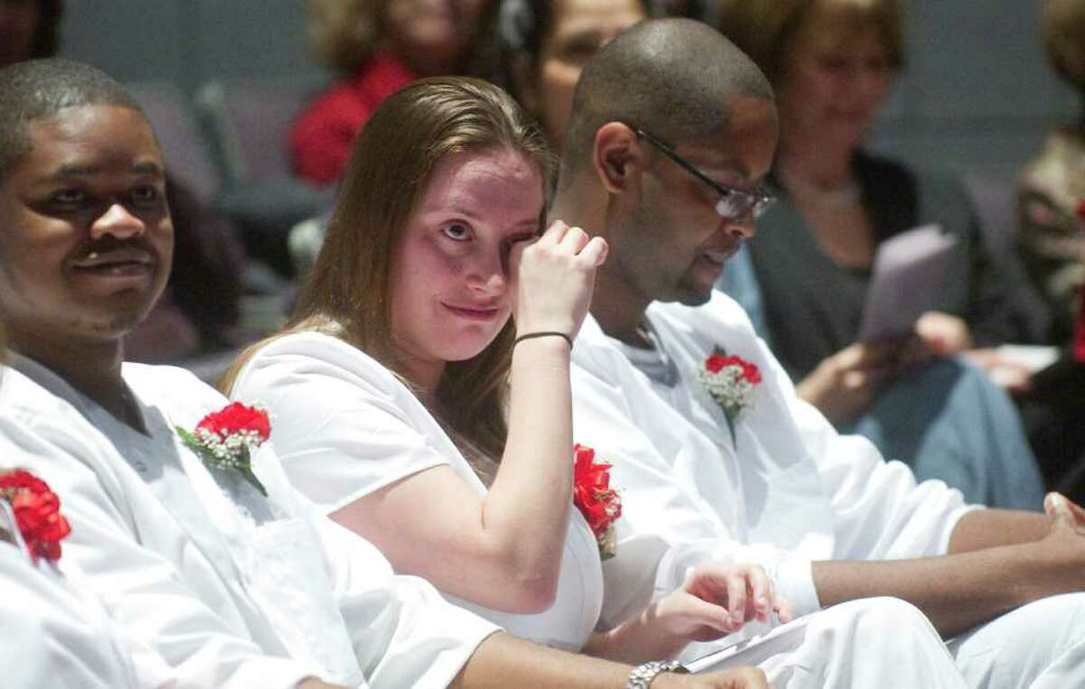 Elizabeth Berry of Fairfield is emotional during the Norwalk Community College Division of Nursing and Allied Health's annual fall Pinning Ceremony in the school's Pepsico Theater in Norwalk, Conn., December 20, 2011. The ceremony is a tradition in which nursing pins are presented to nursing graduation candidates prior to their graduation from NCC.The pinning ceremony represents the symbolic welcoming of newly graduated nurses into the nursing profession. The new nurses are congratulated by the college's nursing faculty, receive a school pin, and participate in a candle lighting ceremony.The tradition dates back 1,000 years and began as a Maltese cross, a symbol of Christianity. Over the centuries, the cross became a coat of arms and eventually morphed into a design that signifies the school from which the nurse has graduated.