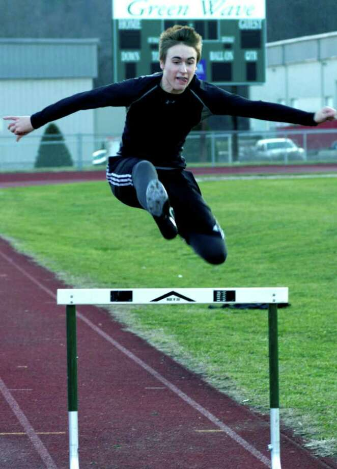 SPECTRUM/Dennis Rafferty of the Green Wave easily soars over a hurdle as the New Milford High School boys' and girls' track teams work in pre-season through the process of just who will be competing in which events this winter. December 2011 Photo: Norm Cummings