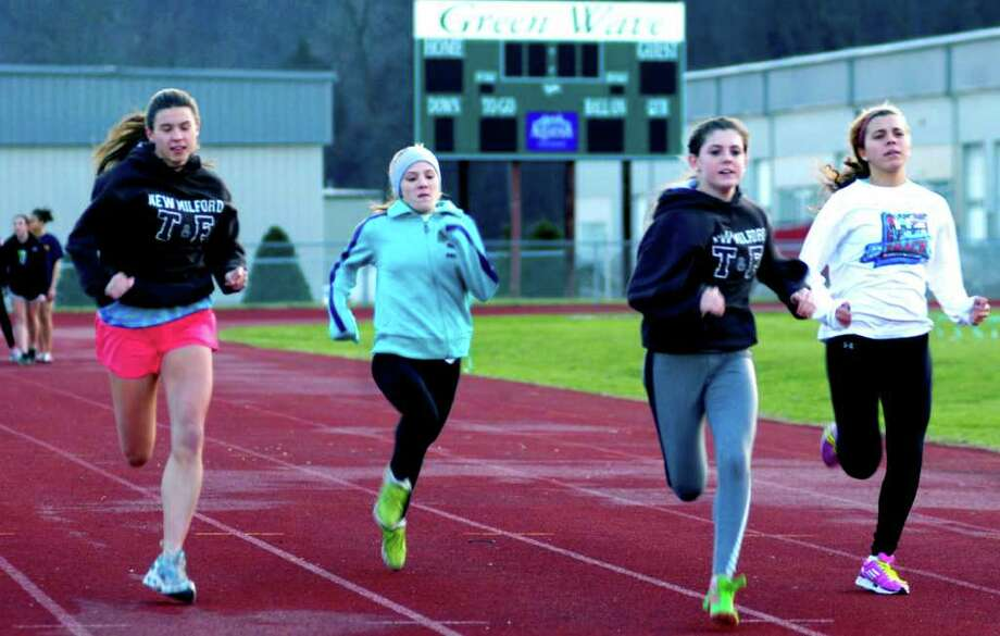 SPECTRUM/Working into competitive condition with sprints on the track are New Milford High School girls' indoor track athletes, from left to right, Lindsay Guptill, Claire Brofford, Meghan Dietter and Evangelia Lambropoulos.  December 2011 Photo: Norm Cummings