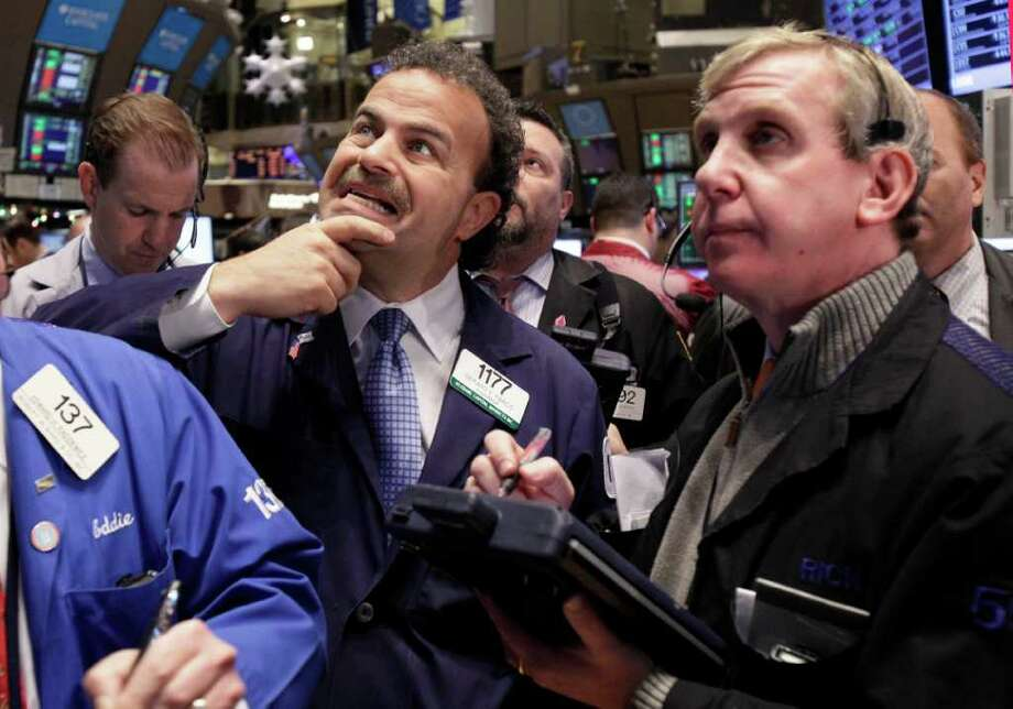 Traders Gerard Farco, left, and Richard Cohen, right. work on the floor of the New York Stock Exchange Tuesday, Dec. 20, 2011. Stocks are surging after the opening bell following encouraging signs out of Europe and a jump in apartment building in the U.S. (AP Photo/Richard Drew) Photo: Richard Drew