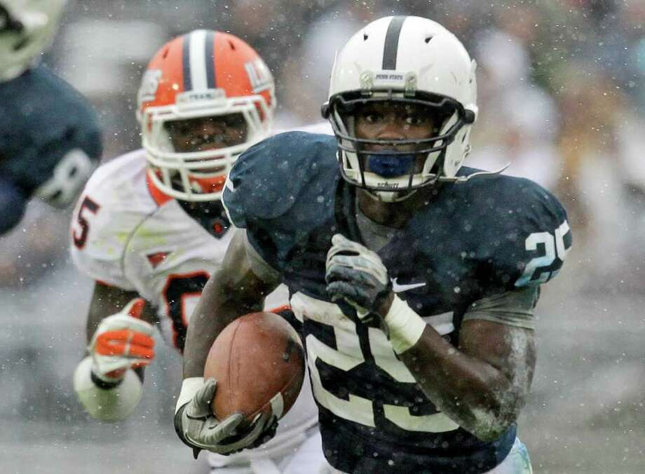 FILE — Penn State running back Silas Redd (25) rushes for 14-yards past Illinois defensive lineman Whitney Mercilus (85)  during the first quarter of an NCAA college football game in State College, Pa., Saturday, Oct. 29, 2011. (AP Photo/Gene J. Puskar) Photo: Gene J. Puskar/Associated Press / AP