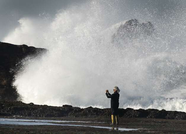 Dolores Silva snaps a photo at low tide near a wall of water crashing against the rocks at Pillar Point near the Maverick's surfing site and Half Moon Bay, Calif., on Wednesday, Jan. 26, 2011. Photo: Paul Chinn, The Chronicle