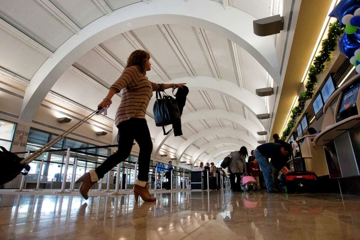 A traveler heads to the check-in kiosks at John Wayne Airport's new Terminal C in Santa Ana, Calif., as she joins fellow travelers in route to their destinations for Thanksgiving, on Wednesday, Nov. 23, 2011. (AP Photo/Los Angeles Times, Allen J. Schaben)