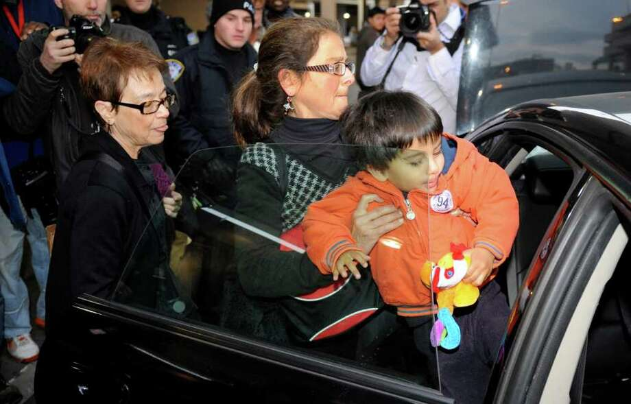 Lori Berenson, center, helps her son Salvador Apari into a waiting car while her mother, Rhoda Berenson, looks on after after Lori and her son arrived from Lima, Peru, at Newark Liberty International Airport, Tuesday, Dec. 20, 2011 in Newark, N.J. Berenson, who was convicted of aiding Peruvian guerrillas and served 15 years before she was paroled last year, said she fully intended to return to Peru by the court-ordered deadline of Jan. 11. (AP Photo/Henny Ray Abrams) Photo: Henny Ray Abrams