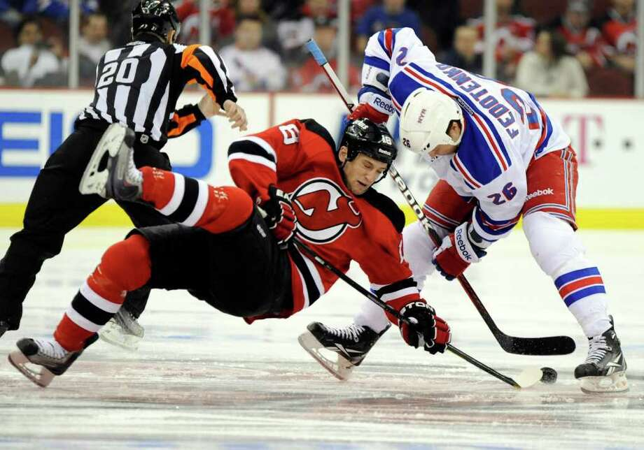 New Jersey Devils' Tim Sestito, left, is knocked off the puck by New York Rangers' Ruslan Fedotenko, of Ukraine, during the first period of an NHL hockey game Tuesday, Dec. 20, 2011, in Newark, N.J. (AP Photo/Bill Kostroun) Photo: Bill Kostroun