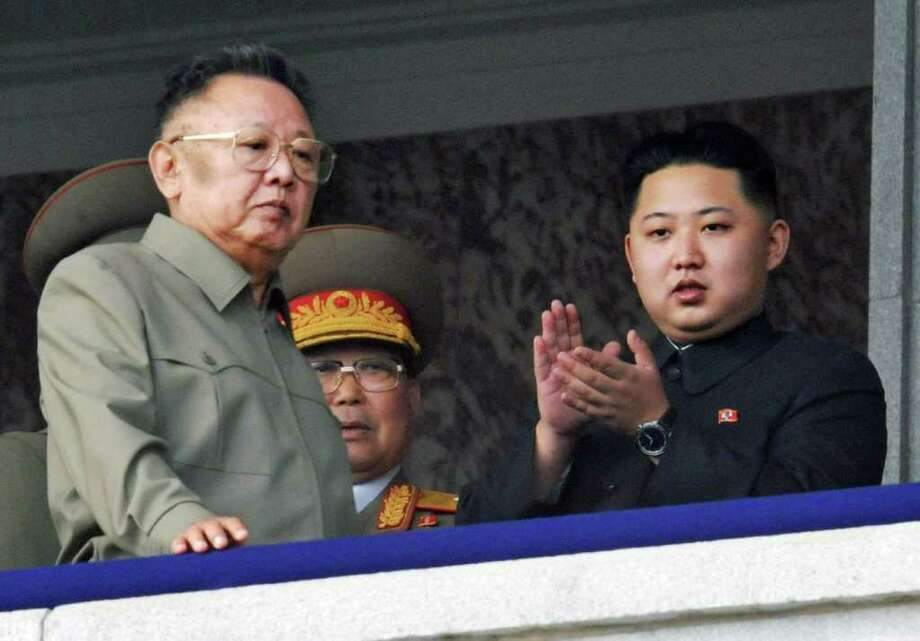 """FILE - In this Oct. 10, 2010 file photo Kim Jong Un, right, along with his father and North Korea leader Kim Jong Il, left, attends during a massive military parade marking the 65th anniversary of the ruling Workers' Party in Pyongyang, North Korea. North Korean television announced Monday, Dec. 19, 2011 in a """"special broadcast"""" that its leader Kim Jong Il has died in Pyongyang. (AP Photo/Kyodo News, File) JAPAN OUT, MANDATORY CREDIT, NO LICENSING IN CHINA, FRANCE, HONG KONG, JAPAN AND SOUTH KOREA / Kyodo News"""