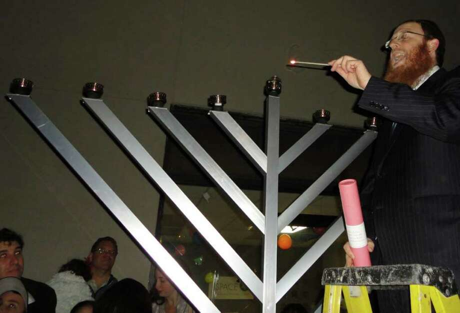 Rabbi Yehuda Kantor of Chabad Lubavitch of Westport on Tuesday lights the center candle on a menorah before lighting the the outer candle, the first one on the first night of Hanukkah, at J Space, the Chabad Community Center in Westport. Photo: Meg Barone / Westport News freelance