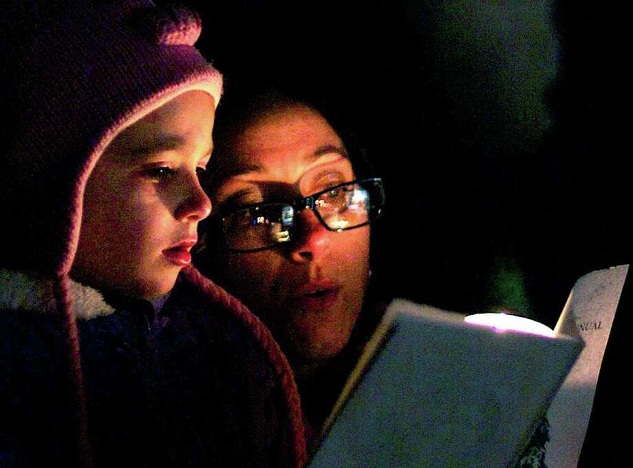 """Singing in the season  SPECTRUM/Hundreds gathered Monday on the Village Green in New Milford for the Commission on the Arts' annual Carol Sing festivities. Above, Harley Pane, 4, of New Preston and her mother, Megan Pane, join in the singing of """"Hark, The Herald Angels Sing."""" For more photos, see S17 Spectrum Images and check www.newmilfordspectrum.com. Dec. 19, 2011 Photo: Trish Haldin"""