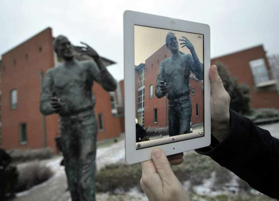 A visitor takes a pictures with an iPad of a statue of the late co-founder of Apple, Steve Jobs, at the Graphisoft Park in the third district of Budapest on December 21, 2011, after the inaugurating ceremony organized by a Hungarian Graphisopt SE for the Apple's legendary founder. The almost two-metre-high (6.5-foot) bronze statue by Hungarian sculptor Erno Toth depicts Jobs with his trademark turtleneck jumper, jeans, sneakers and round glasses. It was erected in a science park that hosts several IT companies, including Graphisoft, which Apple has supported since 1984 when Jobs saw it at the annual CEBIT expo in Hannover, Germany, according to the Hungarian company.  AFP PHOTO / ATTILA KISBENEDEK Photo: ATTILA KISBENEDEK, Getty / AFP