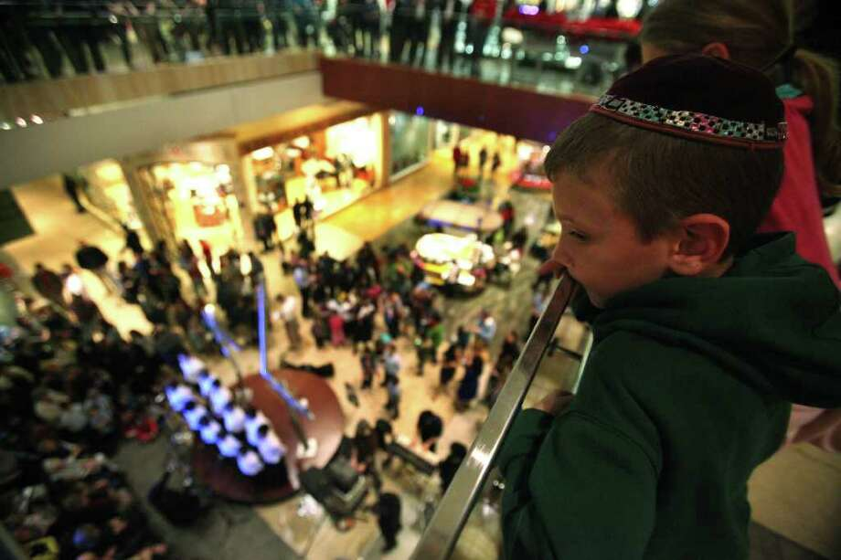 Solomon Dobia, 7, over looks the crowd during the public Menorah Lighting Ceremony on the first night of Hanukkah at the Galleria.  The public menorah was designed by artist Isaac Cohen. Photo: Mayra Beltran, Houston Chronicle / © 2011 Houston Chronicle