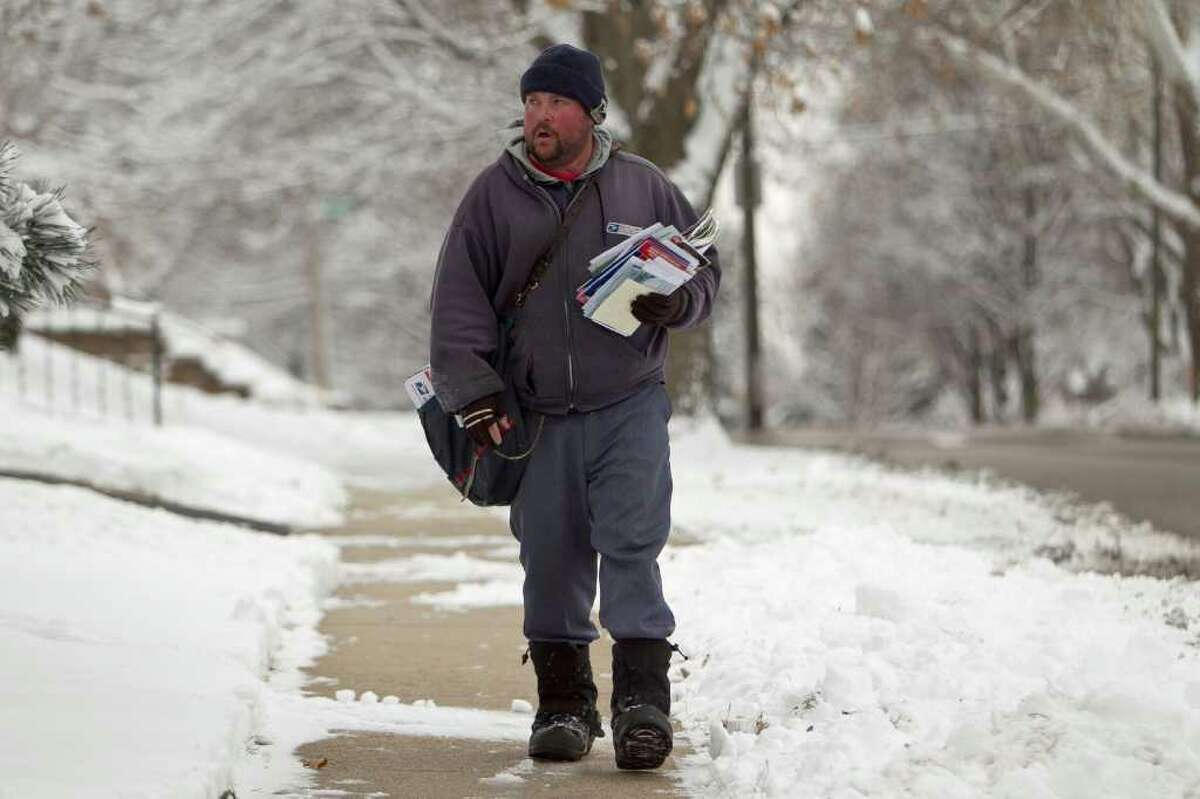 A mail carrier makes his slog in freezing temperatures in Omaha, Neb., in early December. A reader says the USPS is a cornerstone of our communications network and needs to be preserved. He writes that if our electronic communications systems fail, he'd like to have a Plan B, that being the venerable USPS.