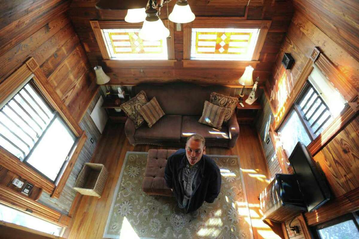 Justin Robinson stands in a small cottage he bought that is made of recycled materials.