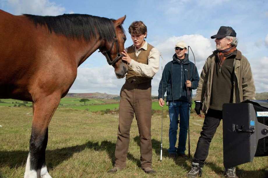 Director Steven Spielberg (far right) observes  Jeremy Irvine (left) rehearse a scene with Joey on the set of DreamWorks Pictures? ?War Horse?, an epic adventure set against a sweeping canvas of rural England and Europe during the First World War. Andrew Cooper/DreamWorks II Distribution Co., LLC. Photo: Andrew Cooper / ©DreamWorks II Distribution Co., LLC.  All Rights Reserved.