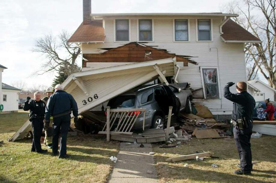 Officers with Norfolk Police Division look over the scene where an SUV crashed into the boyhood home of Johnny Carson in Norfolk, Neb., Tuesday, Dec. 20, 2011. Police say the SUV plowed into the front of the two-story home Tuesday afternoon in Norfolk. The vehicle caused extensive damage to the porch, which collapsed. The vehicle ended up in the entryway. (AP Photo/The Norfolk Daily News, Jake Wragge) Photo: Jake Wragge, Associated Press / Norfolk Daily News