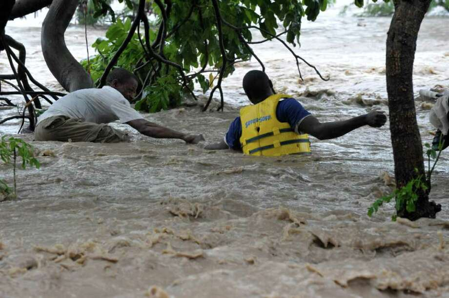 A Tanzanian, left, is rescued by a life saver, right, in yellow jacket in flood water following  fresh flood in Dar es Salaam, Tanzania, Wednesday, Dec. 21, 2011. According to an official at least 8 people are reportedly killed and many others are missing after the city was hit by the worst floods in decades for two consecutive days (AP Photo/ Khalfan Said) Photo: Khalfan Said, Associated Press / AP