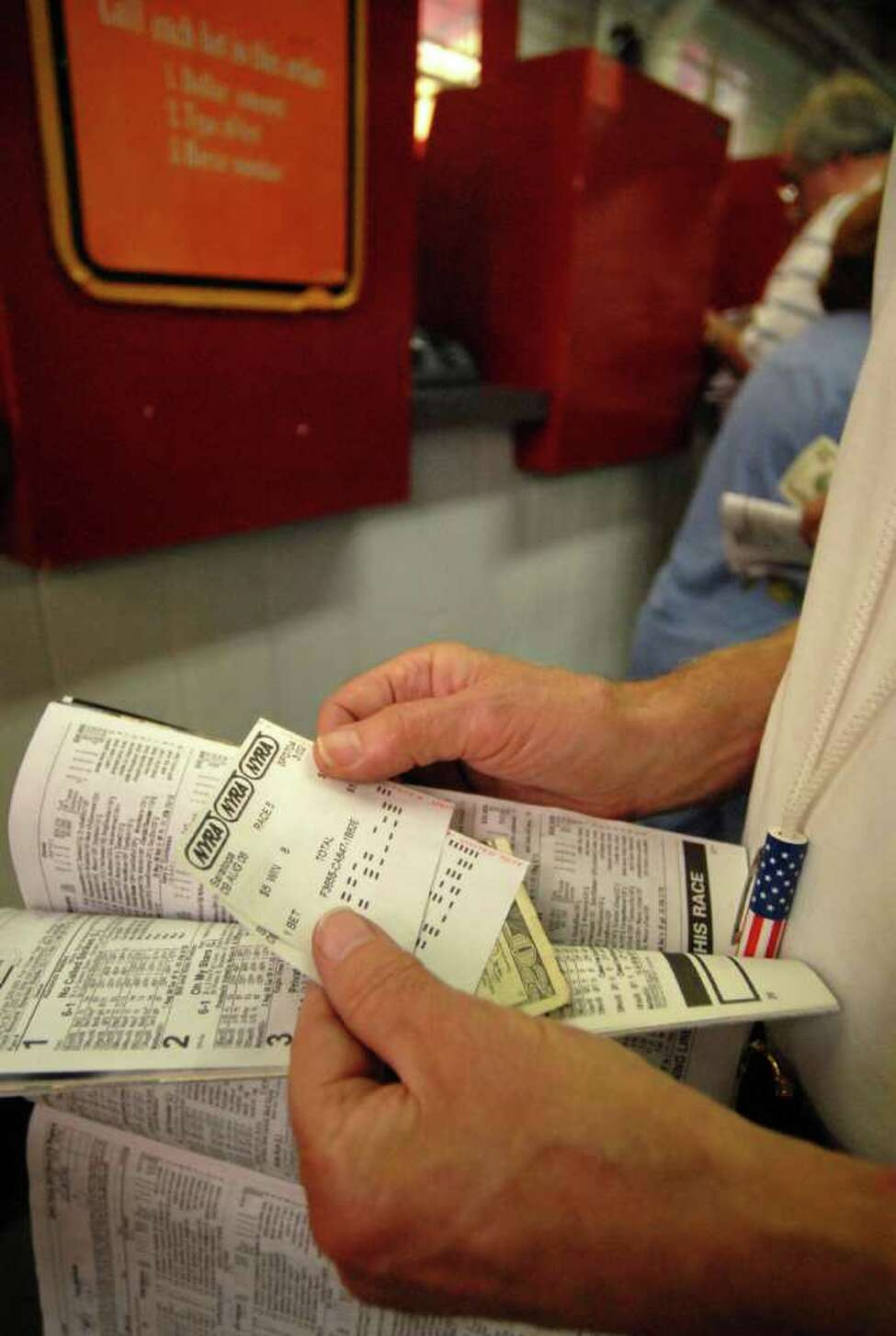 A patron prepares to place a bet and to collect on a winning ticket at the Saratoga Race Course in Saratoga Springs, NY. (Lori Van Buren/Times Union archive)