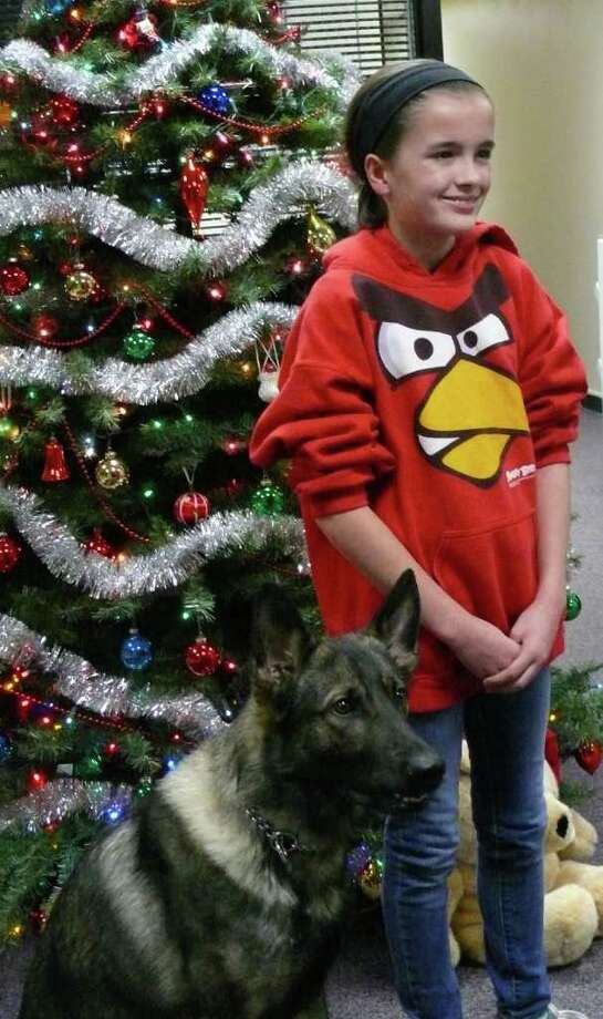 Margaret O'Connell poses with Fairfield's police dog, Ruger, after making a $700 donation to the K9 unit. Photo: Genevieve Reilly / Fairfield Citizen