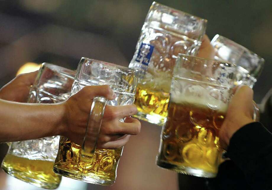 """FILES - Picture taken on September 20, 2009 shows visitors clinking beer mugs during the 176th Oktoberfest beer festival at the """"Theresienwiese"""" in Munich, southern Germany.  Germany's world-famous Oktoberfest beer festival said on May 26, 2010 that it has upped the price for its huge mugs of amber nectar to almost nine euros for this year's 200th anniversary event. AFP PHOTO DDP / OLIVER LANG      GERMANY OUT (Photo credit should read OLIVER LANG/AFP/Getty Images)(Photo Credit should Read /AFP/Getty Images) Photo: OLIVER LANG / DDP"""