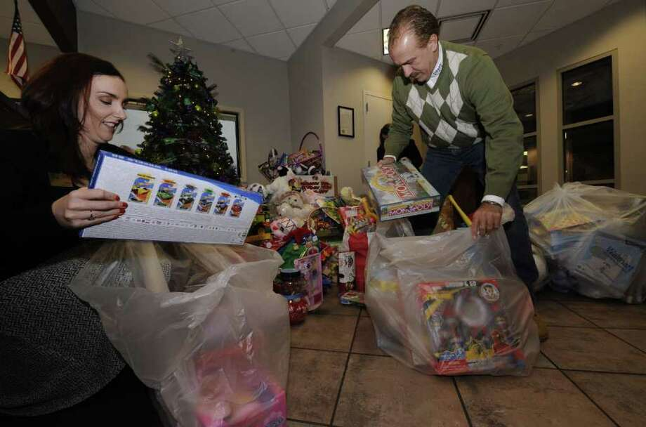 Theresa Petrone, CapCom Foundation Administrator, left assists Lenny Ricchiuti, Director of the Police Athletic League in packing up over 2500 toys received at CapCOM in Colonie, N.Y. Dec. 21, 2011 from branches throughout the area which will be distributed to children in need.     (Skip Dickstein/Times Union) Photo: Skip Dickstein / 00015851A