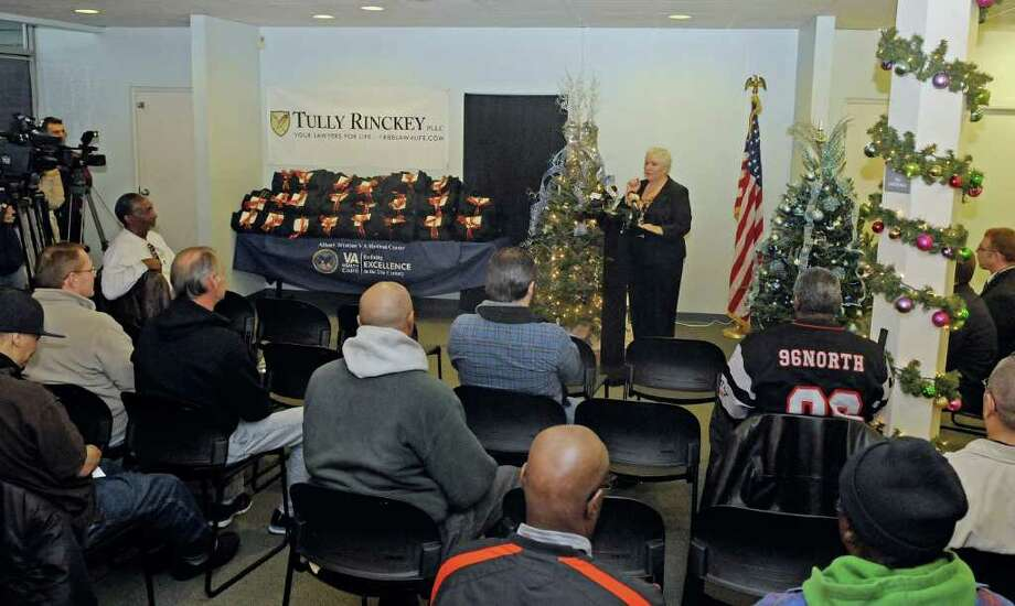 Linda Weiss, at podium, director of the Albany Stratton VA Medical Center, addresses veterans and others gathered at the Veterans Community Service Center on Wednesday, Dec. 21, 2011 in Albany, NY.  The law firm Tully Rinckey distributed coats to veterans in a partnership with Dickies.   (Paul Buckowski / Times Union) Photo: Paul Buckowski / 00015817A