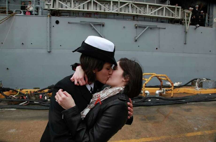 Petty Officer 2nd Class Marissa Gaeta, left, kisses her girlfriend of two years, Petty Officer 3rd Class Citlalic Snell at Joint Expeditionary Base Little Creek in Virginia Beach, Va., Wednesday, Dec. 22, 2011 after Gaeta's ship returned from 80 days at sea. It ís a time-honored tradition at Navy homecomings - one lucky sailor is chosen to be first off the ship for the long-awaited kiss with a loved one. On Wednesday, for the first time, the happily reunited couple was gay.  (AP Photo/The Virginian-Pilot, Brian J. Clark)  MAGS OUT Photo: AP