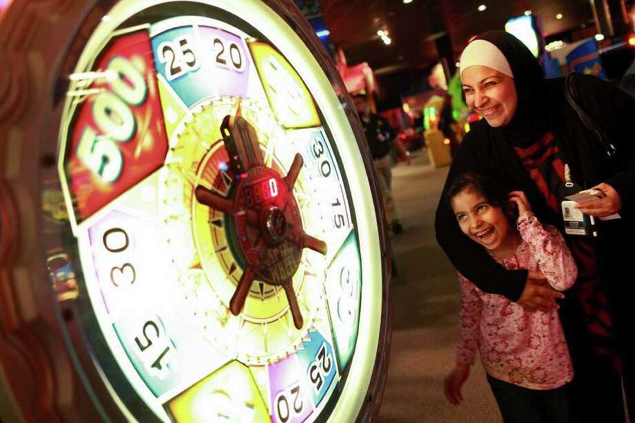 "Zahraa Altayawi, 6, plays ""Treasure Quest"" with her mother, Nagham Saady, originally from Iraq and a caseworker with Catholic Charities Refugee Programs, at The Incredible Pizza Company. Photo: LISA KRANTZ, SAN ANTONIO EXPRESS-NEWS / SAN ANTONIO EXPRESS-NEWS"
