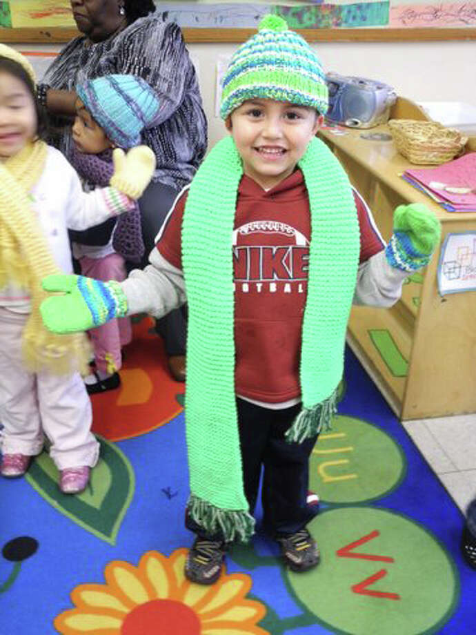 Ian Arriaga, a participant in the NEON Child Development Program, shows off his hat, scarf and mittens made by local RSVP volunteers. Photo: Contributed Photo