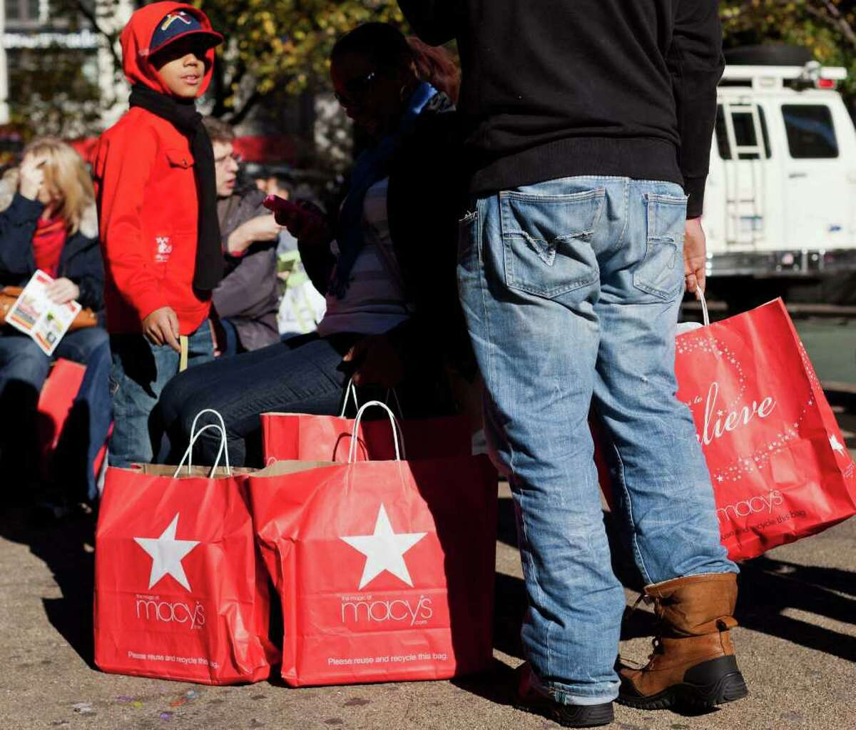 File - In this Nov. 26, 2011 file photo, consumers put down their bags for a rest in Herald Square, in New York. The U.S. economy is ending 2011 on a roll. Growth in the fourth quarter likely accelerated to the fastest pace since mid-2010, and the job market appears to be strengthening.