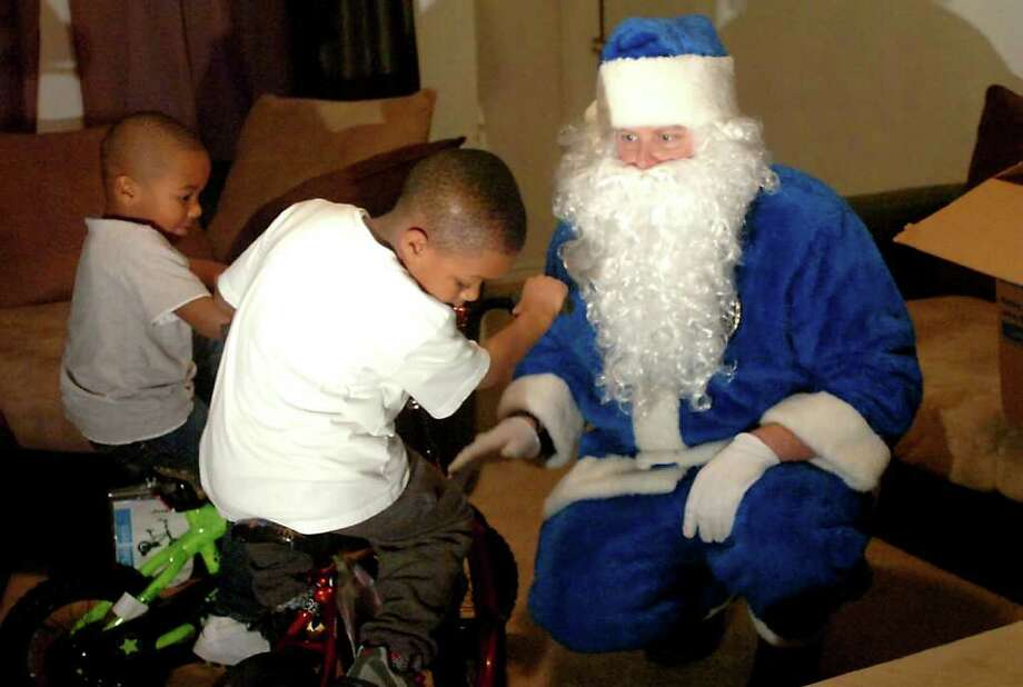 Santa Clause arrives to deliver bikes to Jayden Reed and Jordan Jones in Beaumont, Tuesday, December 20,  2011. The Beaumont Police Department's Santa dressed in blue makes the 23rd annual toy delivery to several families in Beaumont. Tammy McKinley/The Enterprise Photo: TAMMY MCKINLEY