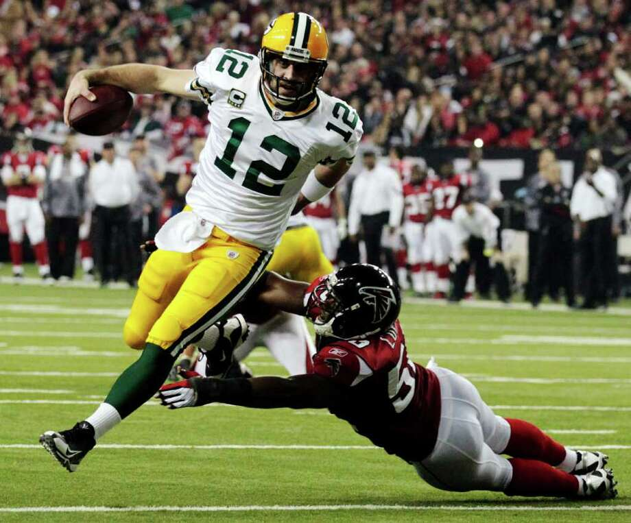 FILE - In this Jan. 15, 2011, file photo, Green Bay Packers quarterback Aaron Rodgers (12) scrambles past Atlanta Falcons linebacker Curtis Lofton (50) on a 7-yard touchdown run during the second half of an NFL divisional playoff football game in Atlanta. Rodgers is the 2011 Male Athlete of the Year chosen by members of The Associated Press after his MVP performance in the Green Bay Packers' Super Bowl victory in February and his stellar play during the team's long unbeaten run this season. (AP Photo/Dave Martin, File) Photo: Dave Martin