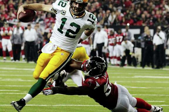 FILE - In this Jan. 15, 2011, file photo, Green Bay Packers quarterback Aaron Rodgers (12) scrambles past Atlanta Falcons linebacker Curtis Lofton (50) on a 7-yard touchdown run during the second half of an NFL divisional playoff football game in Atlanta. Rodgers is the 2011 Male Athlete of the Year chosen by members of The Associated Press after his MVP performance in the Green Bay Packers' Super Bowl victory in February and his stellar play during the team's long unbeaten run this season. (AP Photo/Dave Martin, File)
