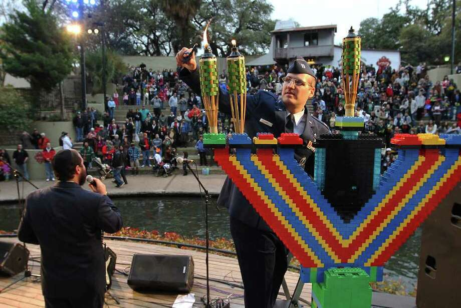 Air Force Chaplain Capt. Michael Bram lights the candles on a menorah made of 4,000 pieces of Legos at the 14th annual Chanukah on the River in 2011. Photo: File Photo, San Antonio Express-News / San Antonio Express-News