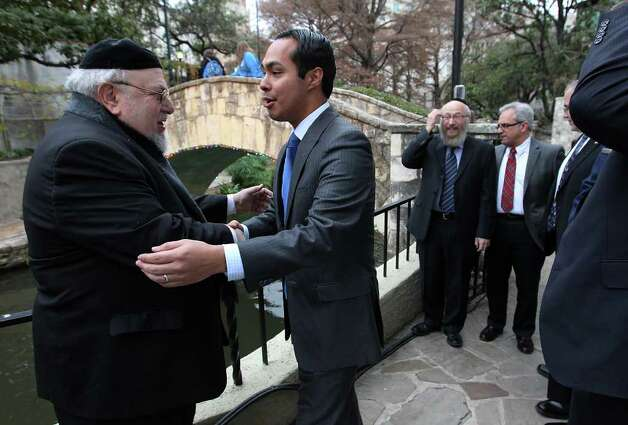 Mayor Julian Castro (center) goes in to hug Rabbi Aryeh Scheinberg (left) at the 14th annual Chanukah on the River on Wednesday, Dec. 21, 2011. The celebration gathered the Jewish community to celebrate the holiday with a boat ride along the RiverWalk and a concert at La Villita's Arneson Theater. Rabbi Chaim Block of Chabad Lubavitch of South Texas has overseen the event since it's inception. The Menorah made of 4,000 Legos was made by the Chabad youth group according to Rabbi Block. Photo: Kin Man Hui, ~ / San Antonio Express-News