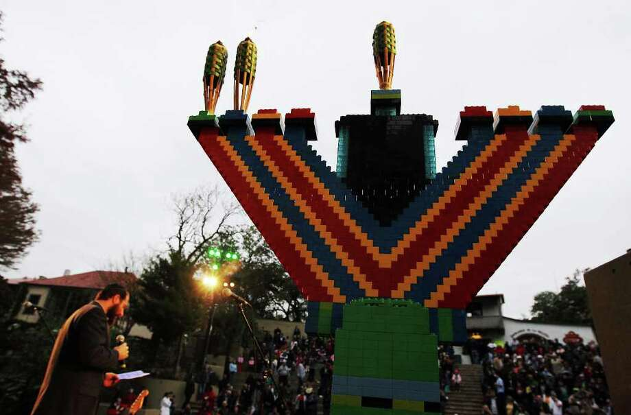 A Menorah made of 4,000 pieces of Legos stands with lit candles to mark the Jewish holiday at the 14th annual Chanukah on the River on Wednesday, Dec. 21, 2011. The Menorah was made by the Chabad youth group according to Rabbi Chaim Block of Chabad Lubavitch of South Texas. Photo: Kin Man Hui, ~ / San Antonio Express-News