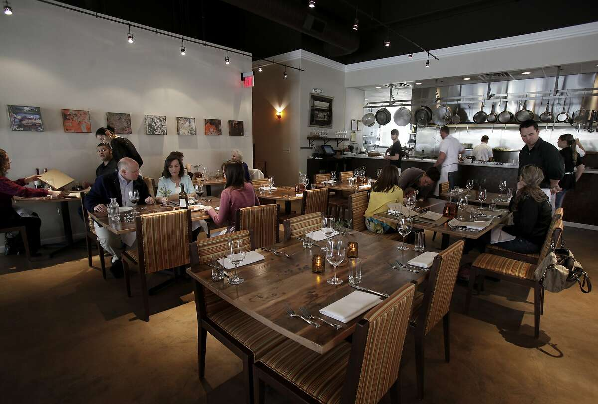 A view of the large dining area in front of the kitchen at Oenotri. Oenotri is a popular restaurant in downtown Napa, Calif. which features a large dining room with a view of the expansive kitchen.