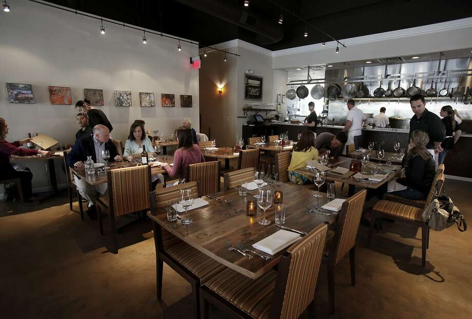 A view of the large dining area in front of the kitchen at Oenotri. Oenotri is a popular restaurant in downtown Napa, Calif. which features a large dining room with a view of the expansive kitchen. Photo: Brant Ward, The Chronicle