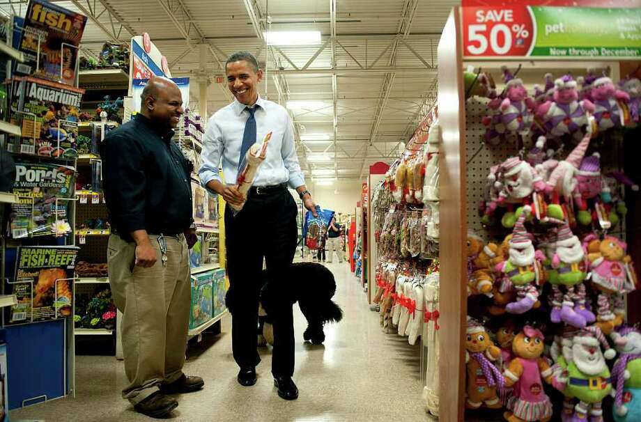 U.S. President Barack Obama, right, shops for Christmas presents with his dog, Bo, at a PetSmart Inc. store in Alexandria, Virginia, U.S., on Wednesday, Dec. 21, 2011. Paychecks for 160 million workers will be reduced in January unless lawmakers break a stalemate that could dent U.S. economic growth and poses political difficulties for a Congress with low public approval ratings. Photo: Kevin Dietsch, Bloomberg / © 2011 Bloomberg Finance LP