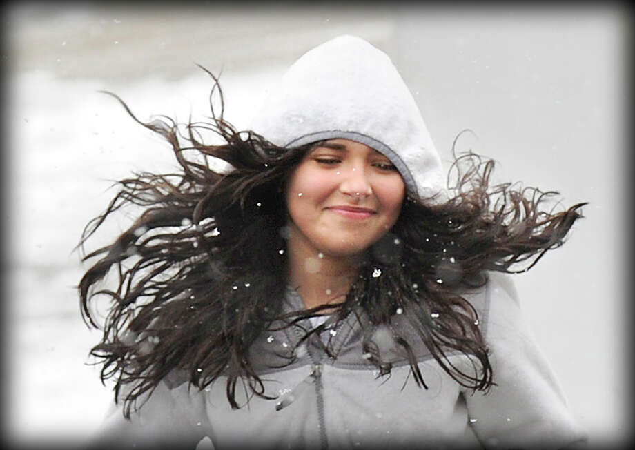 The hair of Samantha Garcia of Greenwich billows out as she dashes across lower Greenwich Avenue during the stor. Photo: Bob Luckey, ST / Greenwich Time