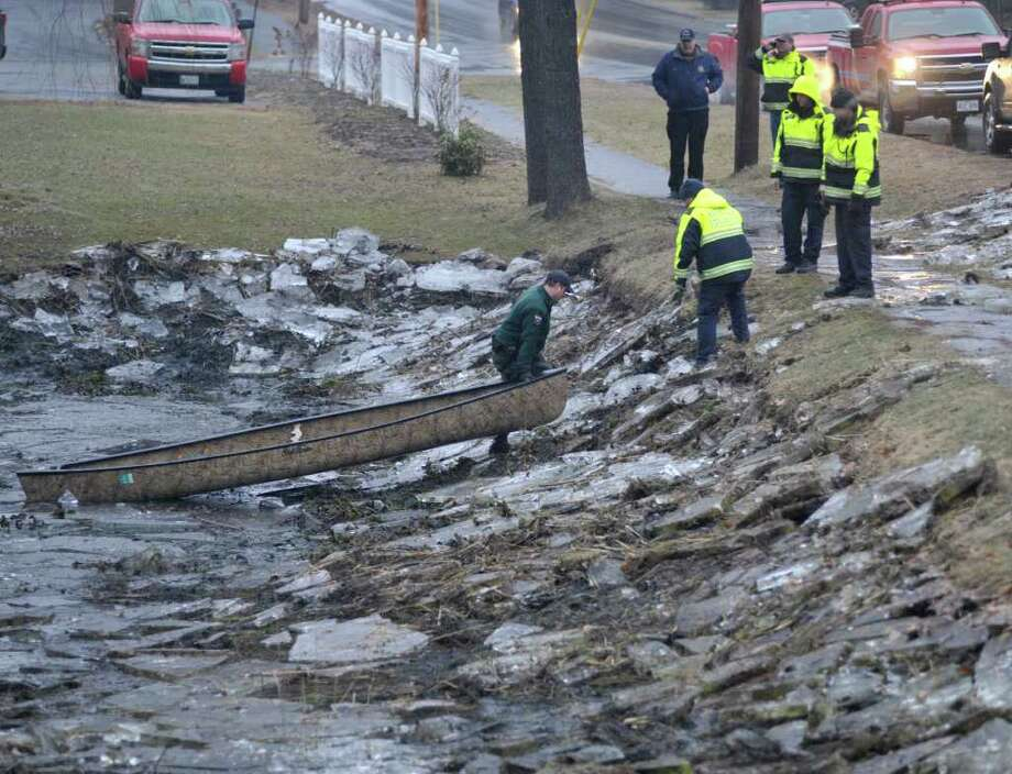 Maine Warden Service personnel aided by Waterville emergency crews search an ice covered drainage pond along First Rangeway Road in Waterville, Maine Wednesday, Dec. 21, 2011. Searchers still hope to find  20 month-old Ayla Reynolds who has been missing since Dec. 16. (AP Photo/Michael C. York) Photo: Michael C. York