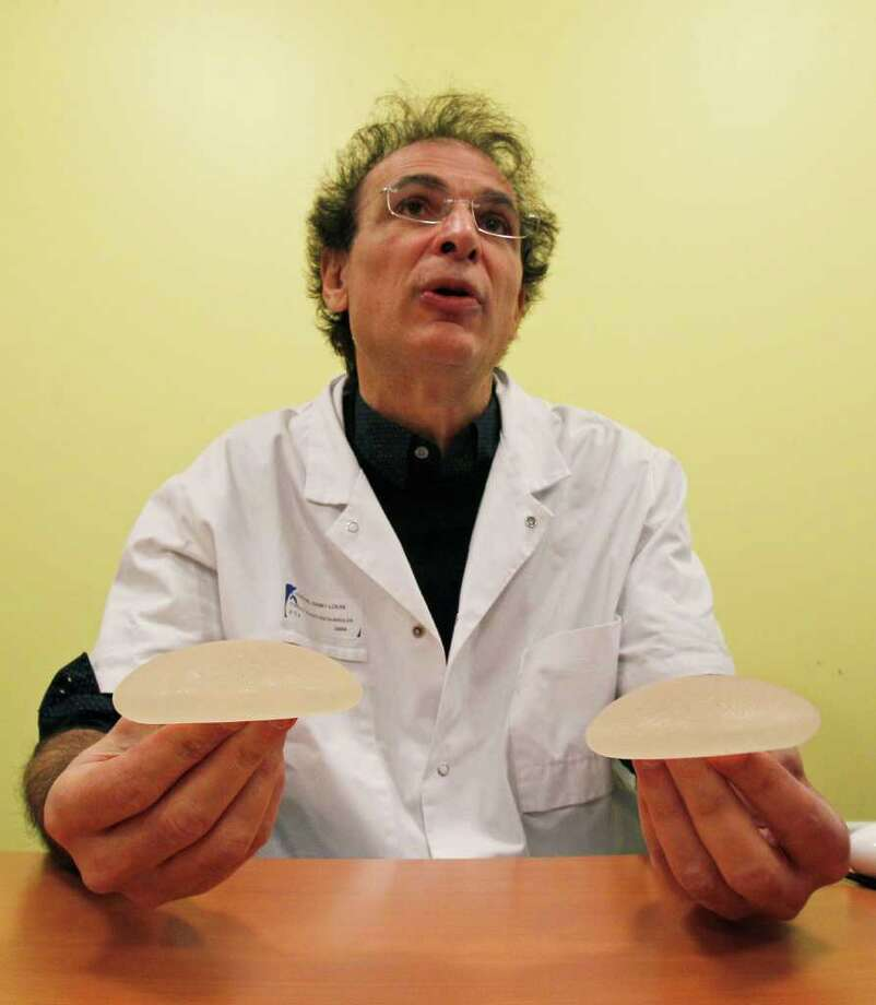 Dr. Maurice Mimoun, a plastic surgeon at the St Louis hospital, holds silicone gel breast implants made by French company Poly Implant Prothese, or PIP, that he removed from a patient because of concerns that they are unsafe, Paris, Wednesday, Dec. 21, 2011. French health authorities are considering whether to suggest that an estimated 30,000 women in France get their breast implants removed, amid warnings by leading doctors about risks of rupture and possible cancer risks. (AP Photo/Michel Euler) Photo: Michel Euler / AP