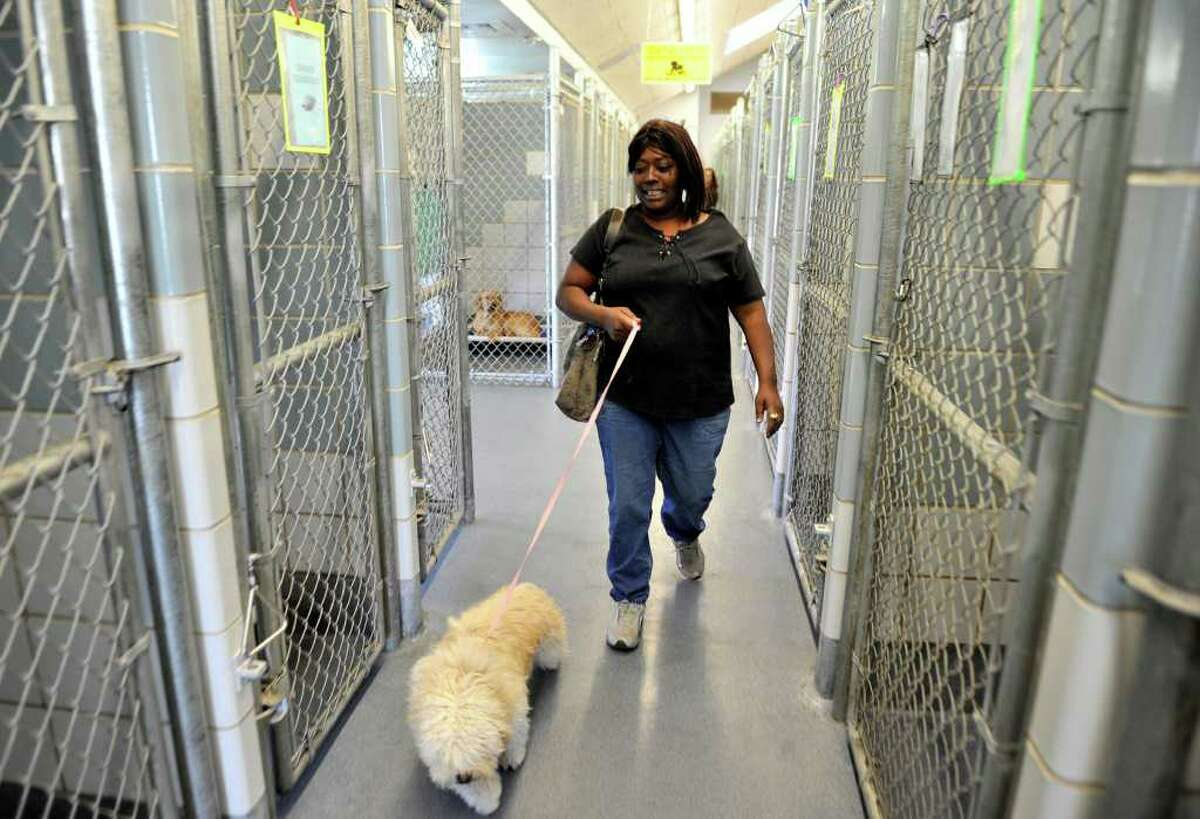 Christine Sattiewhite walks through the Animal Care Services kennel with her recently adopted dog.