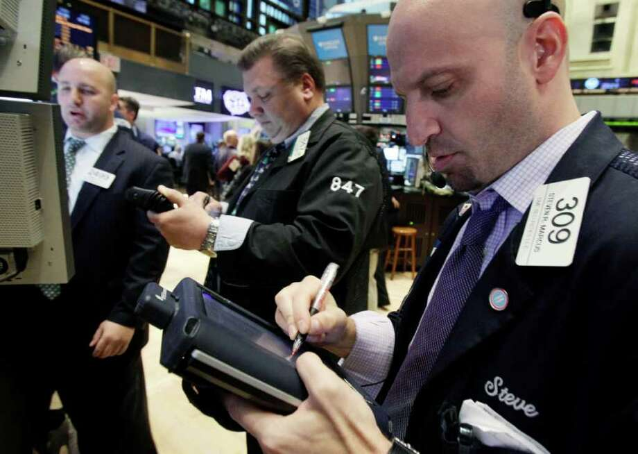 In this Dec. 20, 2011 photo, Steven Marcus, right, works with fellow traders on the floor of the New York Stock Exchange. European stock markets extended gains Wednesday, Dec. 21, on a wave of pre-holiday optimism after the European Central Bank loaned a record amount to the continent's banks in an effort to bolster Europe's stressed financial system. (AP Photo/Richard Drew) Photo: Richard Drew