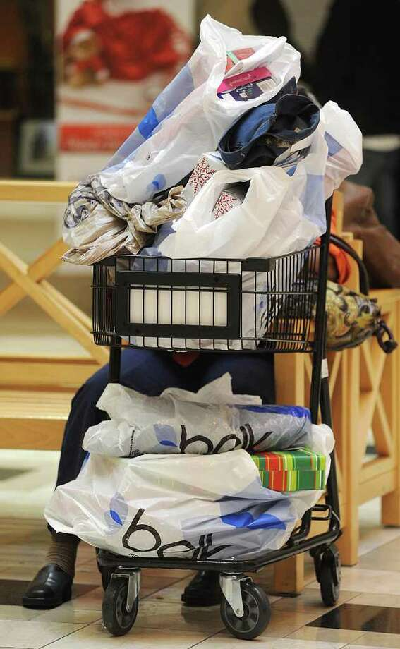 FILE - In this Nov. 25, 2011, file photo, a shopper takes a rest with purchases at Northpark Mall in Ridgeland, Miss. The U.S. economy is ending 2011 on a roll. Growth in the fourth quarter likely accelerated to the fastest pace since mid-2010, and the job market appears to be strengthening.  (AP Photo/The Clarion-Ledger, Vickie D. King, File) NO SALES Photo: Vickie D. King