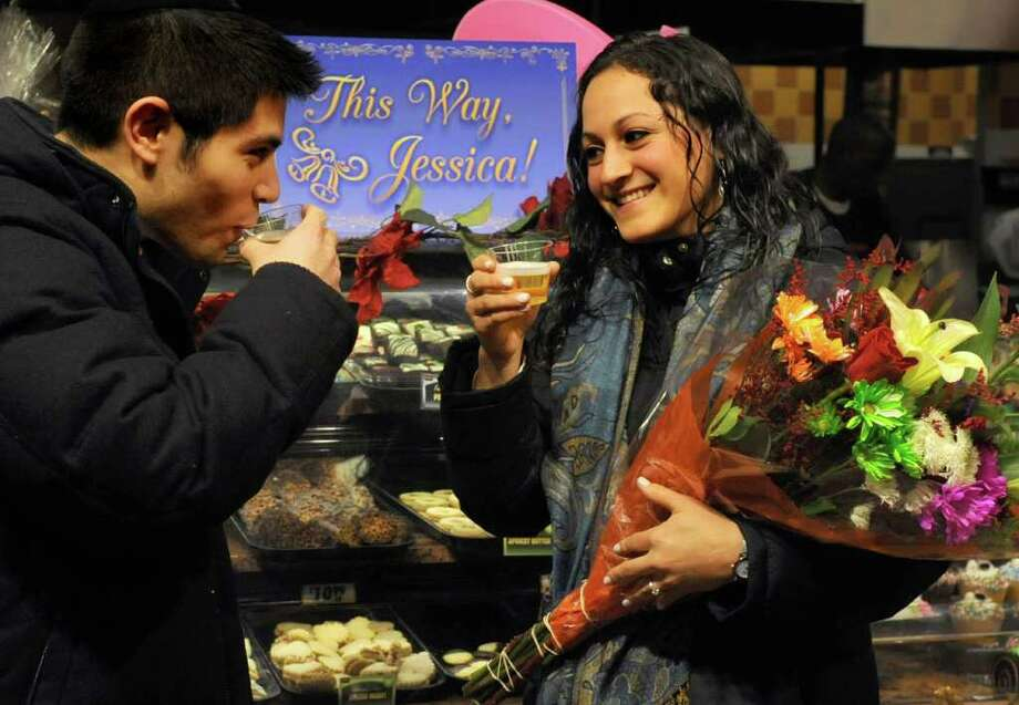 Elie Niedober and Jessica Kfare toast with sparkling cider at Fairway Market after Kfare accepted Niedober's marriage proposal in Stamford on Wednesday, December 21, 2011. Photo: Lindsay Niegelberg / Stamford Advocate
