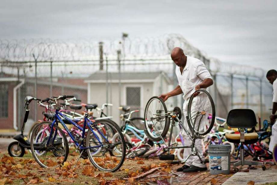 Robert Lee James, an inmate at the Vance Unit, refurbishes bikes that will be delivered to needy kids outside the bicycle shop in Sugar Land. Photo: Nick De La Torre, Houston Chronicle / © 2011  Houston Chronicle