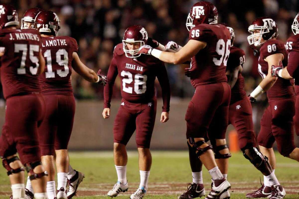 Texas A&M's Randy Bullock (center), who dedicated his senior season to his late father Rich Bullock, recently took home the Lou Groza Award, which is given to the nation's top kicker. (Patrick T. Fallon/The Dallas Morning News)