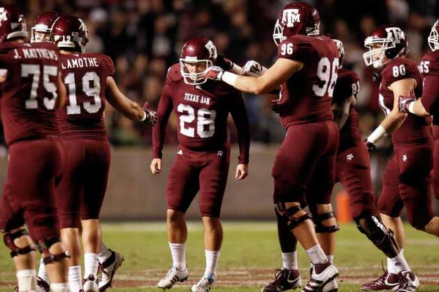 Texas A&M Aggies kicker Randy Bullock (28) is congratulated by his teammates after a kick during the first half of the Texas A&M Aggies vs University of Texas Longhorns rivalry NCAA football game at Kyle Field on Thanksgiving Day, Thursday, November 24, 2011 in College Station, Texas. (Patrick T. Fallon/The Dallas Morning News) Photo: Patrick T. Fallon, Staff Photographer / 10011587B