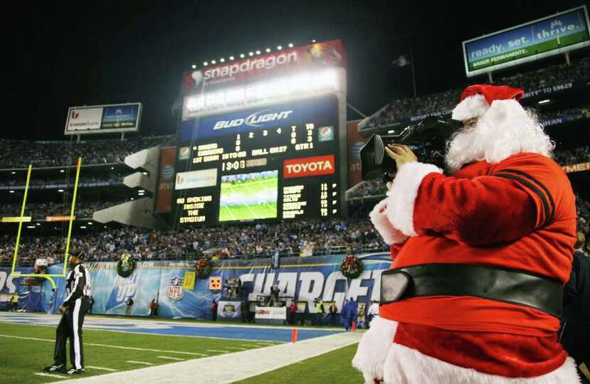 A television cameraman is dressed as Santa Claus during the Baltimore Ravens and San Diego Chargers